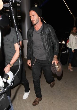 Look de David Beckham: Cazadora de aviador de cuero negra, Camiseta con cuello circular en gris oscuro, Vaqueros negros, Zapatos derby de cuero en marrón oscuro