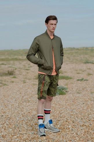 Cómo combinar: cazadora de aviador verde oliva, jersey con cuello circular naranja, pantalones cortos de camuflaje verde oliva, tenis de ante grises