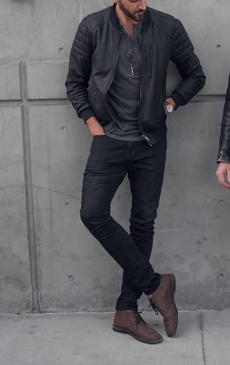 Cómo combinar: cazadora de aviador negra, camiseta henley en gris oscuro, vaqueros negros, botas safari de cuero en marrón oscuro