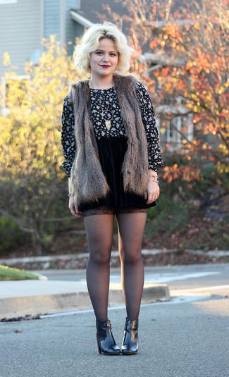 Emparejar un chaleco de pelo marrón oscuro junto a una falda skater de terciopelo negra es una opción estupenda para el fin de semana. Dale un toque de elegancia a tu atuendo con un par de botines de cuero negros.