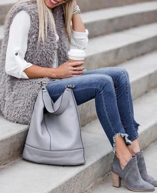Cómo combinar: chaleco de pelo gris, camisa de vestir blanca, vaqueros pitillo azules, botines de ante grises