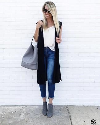 Cómo combinar: chaleco de punto negro, camiseta sin manga blanca, vaqueros pitillo azules, botines de ante grises