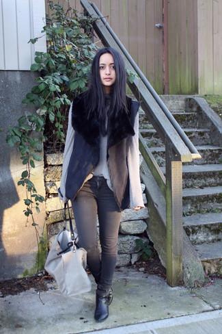 Cómo combinar: chaleco de piel de oveja negro, jersey de cuello alto de punto gris, vaqueros pitillo en gris oscuro, botines de cuero negros