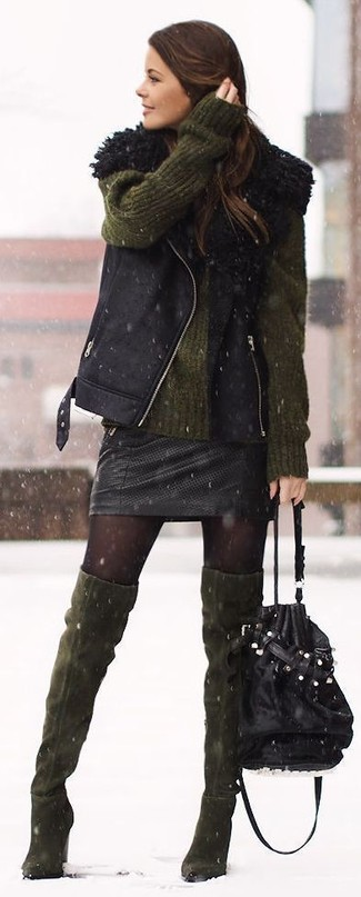 Cómo combinar: chaleco de piel de oveja negro, jersey oversized verde oliva, minifalda de cuero negra, botas sobre la rodilla de ante verde oliva