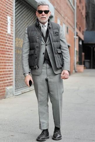 Combinar un chaleco de abrigo acolchado en gris oscuro: Usa un chaleco de abrigo acolchado en gris oscuro y un traje gris para un perfil clásico y refinado. Haz zapatos derby de cuero negros tu calzado para mostrar tu inteligencia sartorial.
