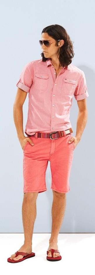 Cómo combinar: correa de lona en multicolor, chanclas rojas, pantalones cortos rosados, camisa de manga corta rosada