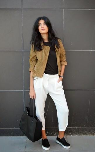 Una chaqueta de ante marrón y unos pantalones pitillo de seda blancos son un look perfecto para ir a la moda y a la vez clásica. ¿Te sientes valiente? Completa tu atuendo con zapatillas slip-on de cuero negras.