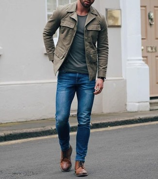 Cómo combinar: chaqueta campo verde oliva, camiseta con cuello circular en gris oscuro, vaqueros pitillo azules, botas brogue de cuero marrónes