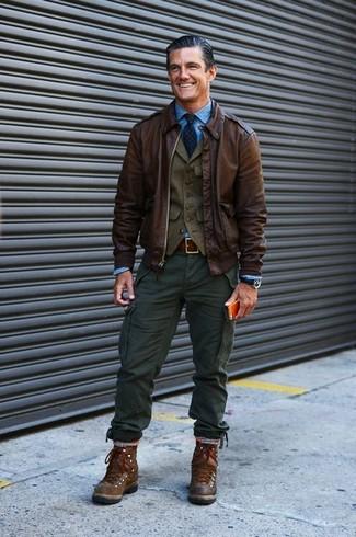 Una camisa de manga larga azul y un pantalón cargo verde oscuro son prendas que debes tener en tu armario. Mezcle diferentes estilos con botas de trabajo de cuero marrón oscuro.
