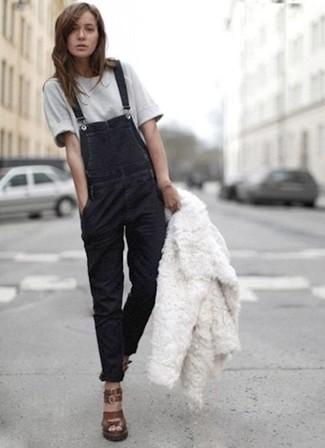 Cómo combinar: chaqueta de piel blanca, camiseta con cuello circular gris, peto vaquero negro, sandalias con cuña de cuero en marrón oscuro
