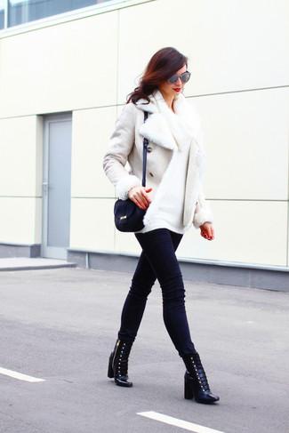 Cómo combinar: chaqueta de piel de oveja blanca, jersey con cuello vuelto holgado blanco, vaqueros pitillo negros, botines con cordones de cuero negros