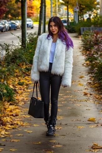 La versatilidad de una chaqueta de piel blanca y unos vaqueros pitillo negros los hace prendas en las que vale la pena invertir. Haz este look más informal con botas a media pierna de cuero negras.