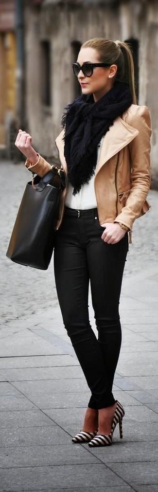 Empareja una chaqueta motera de cuero marrón claro junto a unos vaqueros pitillo negros para un almuerzo en domingo con amigos. Zapatos de tacón de cuero de rayas horizontales negros y blancos proporcionarán una estética clásica al conjunto.
