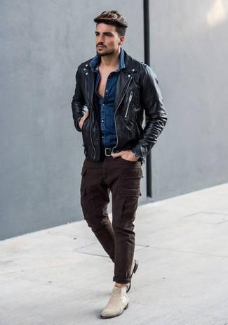 Cómo combinar: chaqueta motera de cuero negra, camisa vaquera azul marino, pantalón cargo en marrón oscuro, botines chelsea de ante en beige