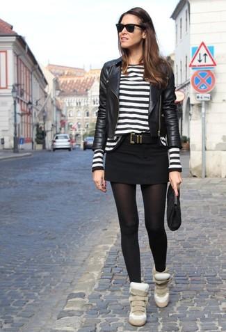 Elige una chaqueta motera de cuero negra y una minifalda para una apariencia fácil de vestir para todos los días. Zapatillas con cuña de ante beige son una sencilla forma de complementar tu atuendo.