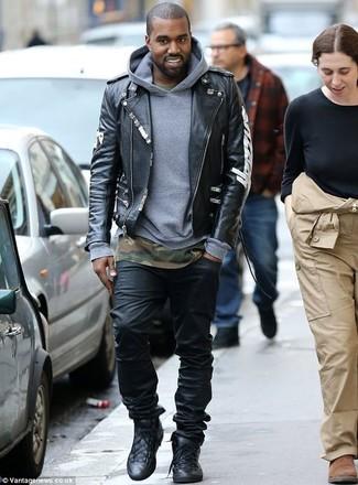 Look de Kanye West: Chaqueta Motera de Cuero Estampada Negra, Sudadera con Capucha Gris, Camiseta con Cuello Circular de Camuflaje Verde Oliva, Vaqueros Negros