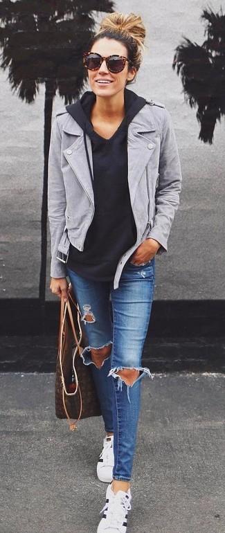 Empareja una chaqueta motera de ante gris con unos vaqueros pitillo desgastados azules y te verás como todo un bombón. Para darle un toque relax a tu outfit utiliza tenis de rayas horizontales en blanco y negro.