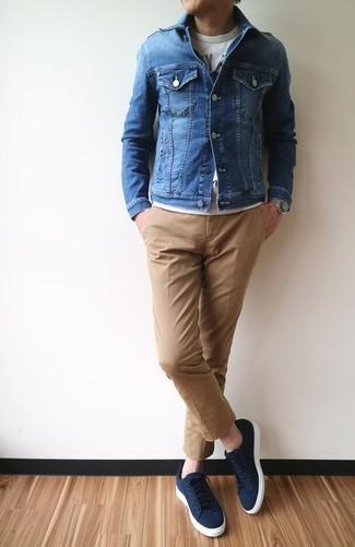 Cómo combinar: chaqueta vaquera azul, camiseta con cuello circular estampada gris, pantalón chino marrón claro, tenis de lona azul marino