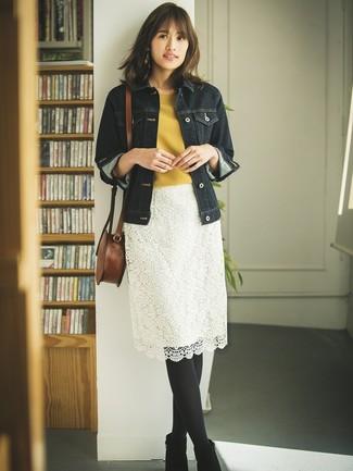 Cómo combinar: chaqueta vaquera azul marino, jersey de manga corta mostaza, falda lápiz de encaje blanca, botines de ante negros