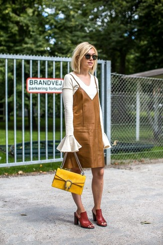 Cómo combinar: bolso de hombre de ante amarillo, chinelas de cuero burdeos, vestido camisola de cuero marrón claro, jersey de pico blanco