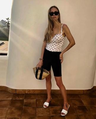 Cómo combinar: bolsa tote de paja marrón claro, chinelas de cuero blancas, mallas ciclistas negras, corsé a lunares en blanco y negro