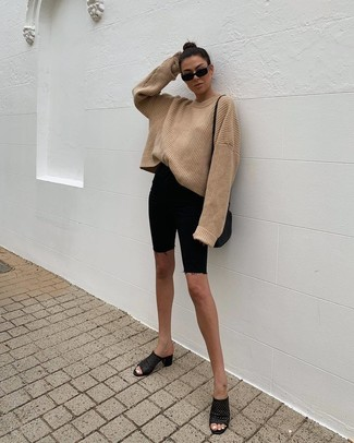 Cómo combinar: bolso bandolera de cuero negro, chinelas de cuero negras, mallas ciclistas vaqueras negras, jersey oversized de punto marrón claro