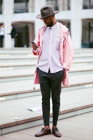 Cómo combinar: chubasquero rosado, camisa de manga larga de rayas verticales rosada, pantalón chino negro, zapatos oxford de cuero en marrón oscuro