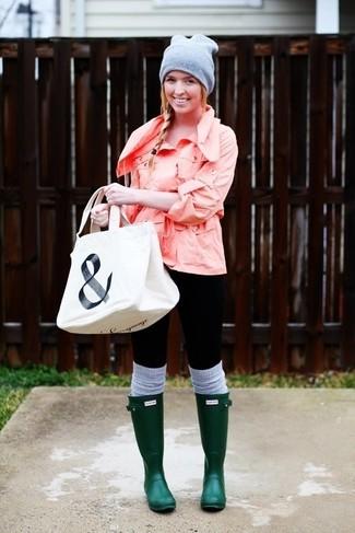 Look de moda: Chubasquero Rosado, Leggings Negros, Botas de Lluvia Verde Oscuro, Bolsa Tote de Lona Estampada Blanca y Negra