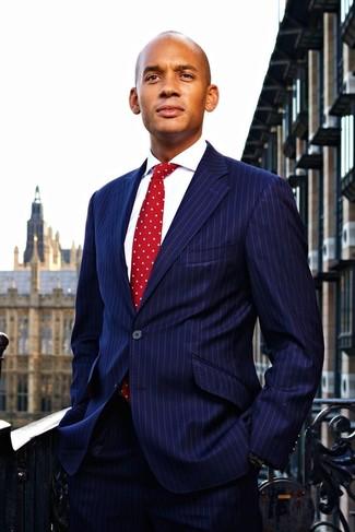 Combinar una corbata a lunares roja: Ponte un traje de rayas verticales azul marino y una corbata a lunares roja para una apariencia clásica y elegante.