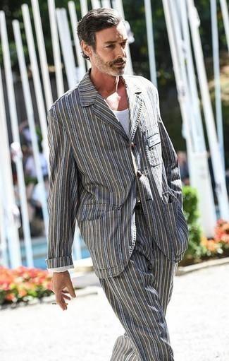 Combinar un traje de rayas verticales gris: Si buscas un look en tendencia pero clásico, ponte un traje de rayas verticales gris y una camiseta sin mangas blanca.
