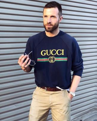 Cómo combinar: reloj plateado, correa de cuero en marrón oscuro, pantalón chino en beige, jersey con cuello circular estampado azul marino