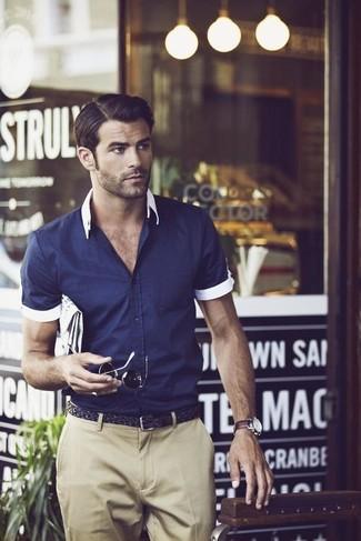Cómo combinar: reloj de cuero en marrón oscuro, correa de cuero tejida negra, pantalón chino en beige, camisa de manga corta azul marino