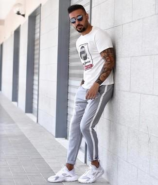 Look de moda: Gafas de sol azul marino, Deportivas blancas, Pantalón chino gris, Camiseta con cuello circular estampada blanca