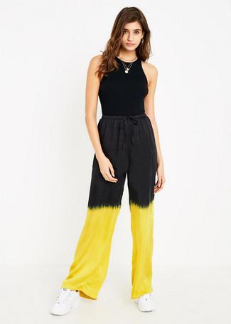 Cómo combinar: colgante dorado, deportivas blancas, pantalones anchos efecto teñido anudado amarillos, camiseta sin manga negra