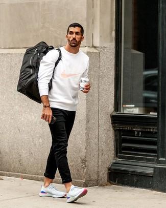 Cómo combinar: bolso baúl de lona negro, deportivas blancas, vaqueros negros, sudadera estampada blanca