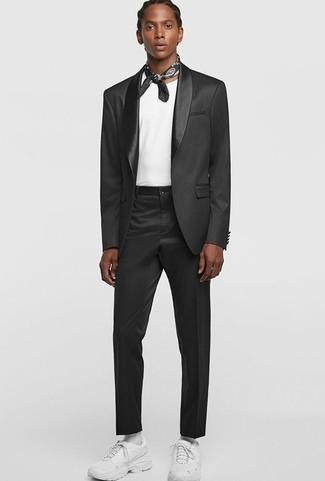 Outfits hombres: Usa un traje en gris oscuro y una camiseta con cuello circular blanca para un lindo look para el trabajo. ¿Por qué no añadir deportivas blancas a la combinación para dar una sensación más relajada?