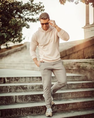 Cómo combinar: deportivas de ante en beige, pantalón chino gris, sudadera con capucha en beige