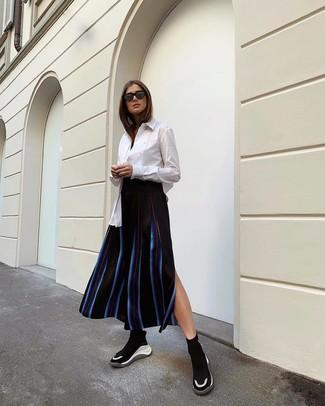 Combinar unas deportivas en negro y blanco: Elige una camisa de vestir blanca y una falda midi de rayas verticales negra para después del trabajo. Deportivas en negro y blanco añaden un toque de personalidad al look.
