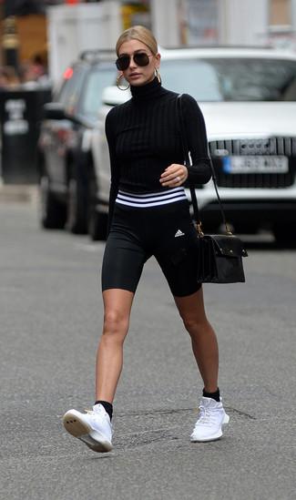 Cómo combinar: bolso bandolera de cuero negro, deportivas blancas, mallas ciclistas en negro y blanco, jersey de cuello alto negro