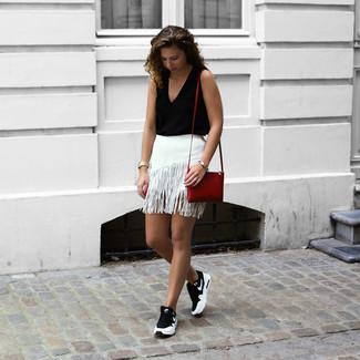 Cómo combinar: bolso bandolera de cuero rojo, deportivas en negro y blanco, minifalda сon flecos blanca, blusa sin mangas negra