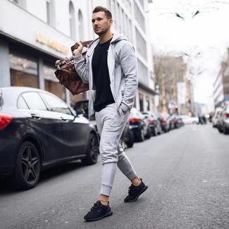 Cómo combinar: bolsa de viaje de cuero marrón, deportivas negras, chándal gris, camiseta con cuello circular negra