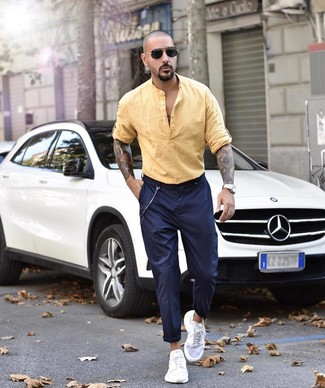 Cómo combinar: gafas de sol negras, deportivas blancas, pantalón chino de rayas verticales azul marino, camisa de manga larga de lino amarilla