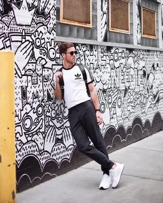 Cómo combinar: mochila de cuero negra, deportivas blancas, pantalón chino en gris oscuro, camiseta con cuello circular estampada en blanco y negro
