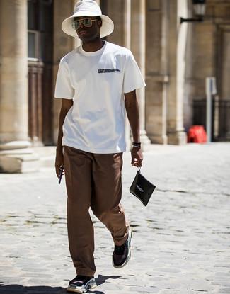 Cómo combinar: bolso con cremallera de cuero estampado en negro y blanco, deportivas negras, pantalón chino marrón, camiseta con cuello circular estampada en blanco y negro