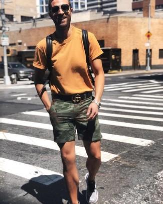 Cómo combinar: mochila de cuero negra, deportivas grises, pantalones cortos de camuflaje verde oliva, camiseta con cuello circular naranja
