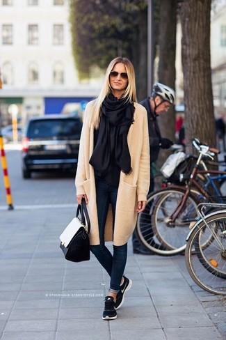 Cómo combinar: bolso de hombre de cuero en negro y blanco, deportivas azul marino, vaqueros pitillo azul marino, abrigo en beige