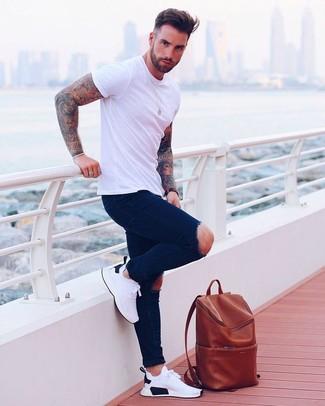 Cómo combinar: mochila de cuero en tabaco, deportivas blancas, vaqueros pitillo desgastados azul marino, camiseta con cuello circular blanca