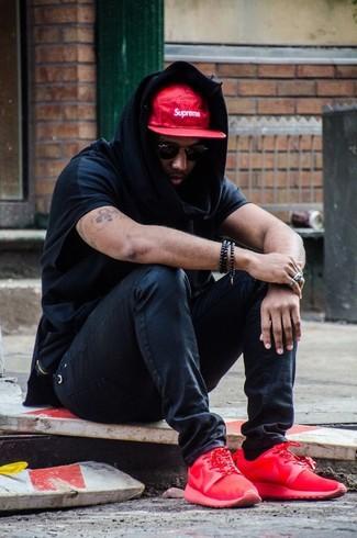 Cómo combinar: gorra de béisbol estampada en rojo y blanco, deportivas rojas, vaqueros pitillo negros, sudadera con capucha negra