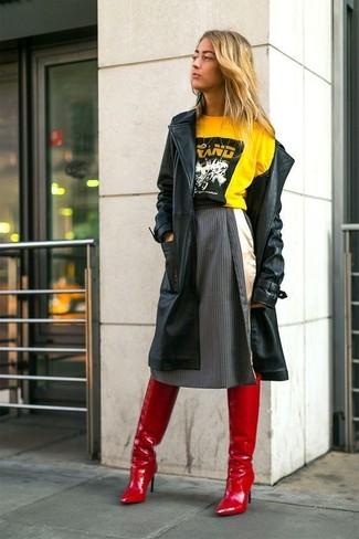 Cómo combinar: botas sobre la rodilla de cuero rojas, falda campana de rayas verticales en gris oscuro, camiseta con cuello circular estampada amarilla, gabardina de cuero negra