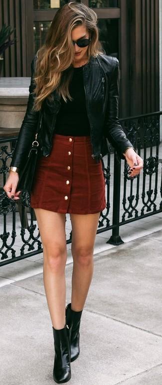 Cómo combinar: botines de cuero negros, falda con botones de ante roja, camiseta con cuello circular negra, cazadora de aviador de cuero negra